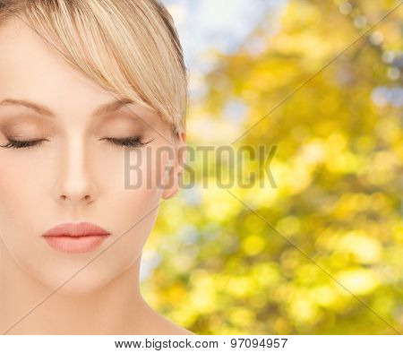 beauty, people and health concept - beautiful young woman face in make-up over yellow autumn background
