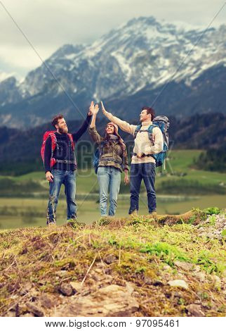 adventure, travel, tourism, hike and people concept - group of smiling friends with backpacks making high five gesture over mountains background