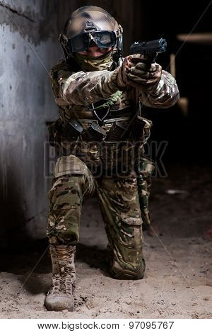 Armed Man In Military Camouflage Aiming His Gun On Knees