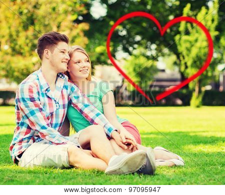 holiday, valentine's day, dating and love concept - happy couple sitting on grass in summer park with red heart shape