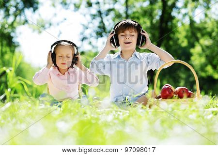 Cute boy and girl in summer park listening to music