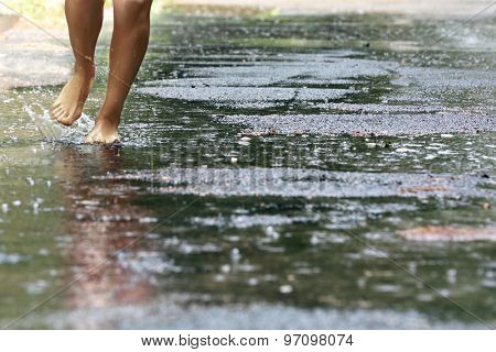 Woman walking barefoot through puddle outdoors