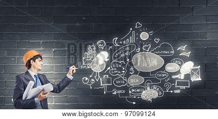 Young man engineer in helmet drawing business plan