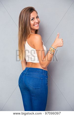 Rear view portrait of a smiling young girl looking back at camera and showing thumb up over gray background