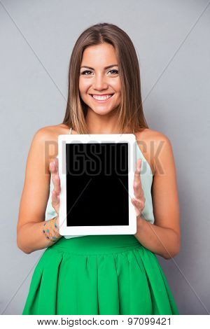 Smiling girl showing tablet computer screen over gray background. Looking at camera