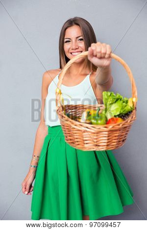 Portrait of a happy beautiful woman holding basket with vegetables over gray background