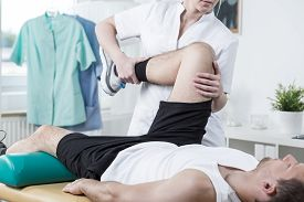 picture of physiotherapist  - Female physiotherapist training leg of young man - JPG