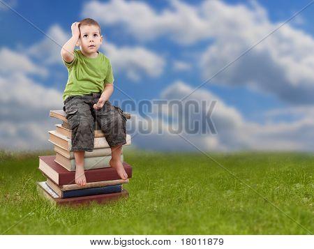 Child Sitting On Books