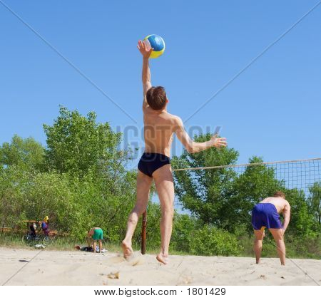Two Men Play Beach Volleyball - Short Guy Serves The Ball