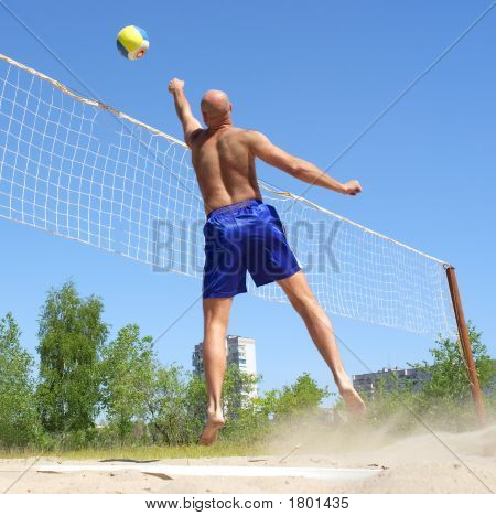 Bald Man Plays Beach Volleyball - Jumping Above Net