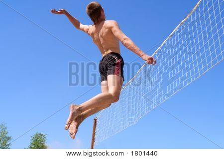 Teenager Jumps High For Spike While Playing Beach Volleyball
