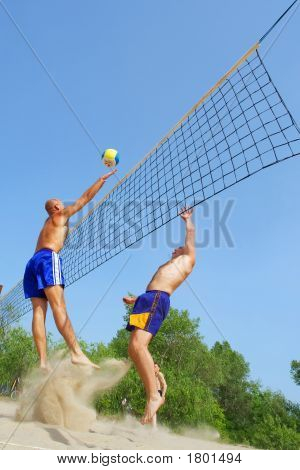 Three Men Playing Beach Volleyball - Balding Man Strikes Ball Over Net