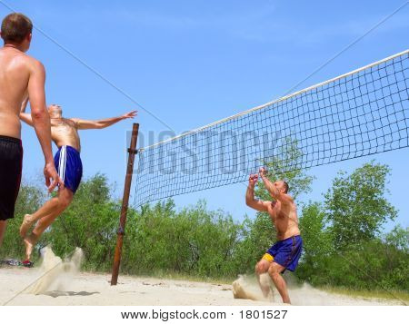 Three Men Playing Beach Volleyball - One Watches, One Spikes, One Prepares To Block