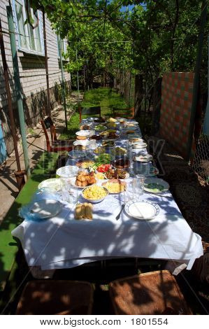 Big Lunch Table With Many Countryside Dishes In Shadow Of Grape Leaves In Hot Sunny Day