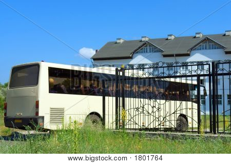 Big Bus Enters The Gate Into A Big Hotel
