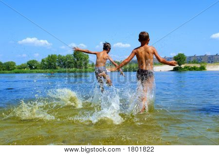 Two Boys Run Into Water With Lots Of Splashes