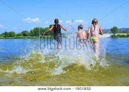 Stoßen Sie drei Kinder, zwei Mädchen und jungen, mit Spritzern Wasser