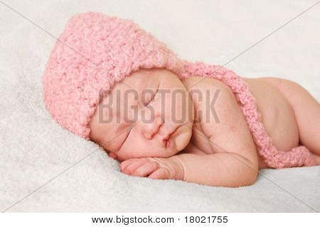 Newborn baby girl wearing a pink knitted elf hat.