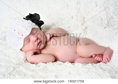 Newborn baby girl sleeping wearing a knitted hat.