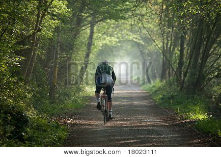 Older man cycling into distance