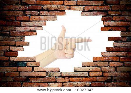 porous wall see woman hand as gun