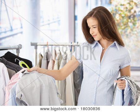 Young Woman looking at Shirt Kleider vorrätig lächelnd.?