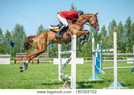 poster of The rider on the show jumper horse overcome high obstacles in the arena for show jumping on background blue sky
