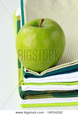 Pile of linen kitchen towels with green apple