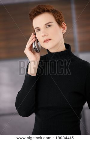 Young trendy woman wearing polo-neck top concentrating on mobile phone call.?