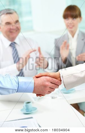 Photo of handshake of business partners after striking deal on background of two partners applauding