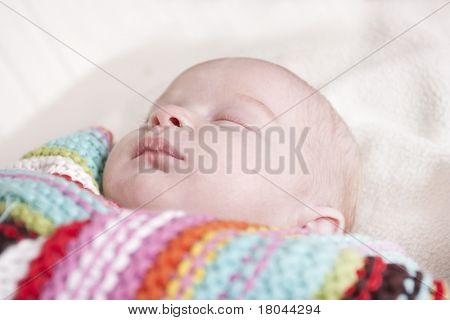 newborn baby wrapped up asleep in a stripey shawl