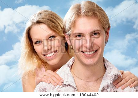 Closeup portrait of a smiling young couple together over a blue sky