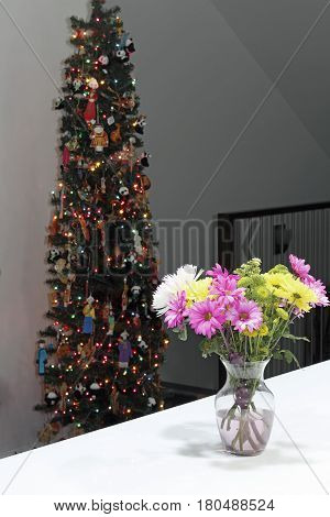 Inside a home at night a beautiful floral bouquet in a vase with a decorated a Christmas tree. Vibrant flowers bouquet and Christmas tree in the background.