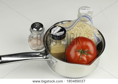 Gathered with a pan is tomato garlic powder white quinoa basil and pink salt. Ingredients of vegetables white organic quinoa and pink salt with a saucepan.
