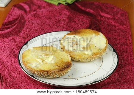 One everything bagel sliced in half toasted and buttered placed on a plate over a red place mat. Bagel with seeds toasted and buttered on a dish.