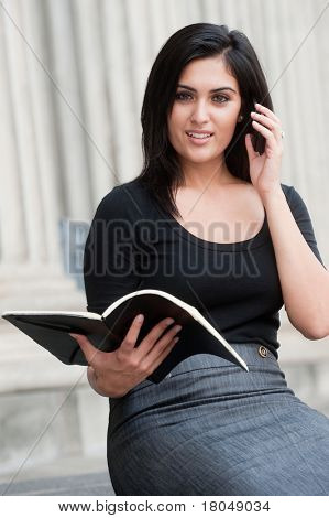 An attractive Indian businesswoman sitting outside with phone and a notebook
