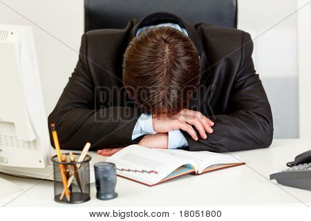 Tired business man sleeping at desk in office