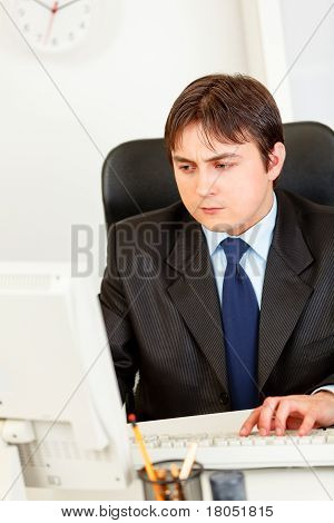 Concentrated modern business man sitting at office desk and working on computer
