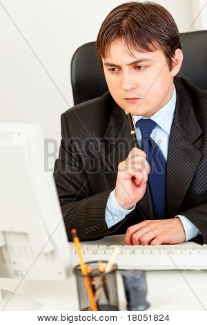 Thoughtful modern businessman sitting at office desk and looking at computer monitor