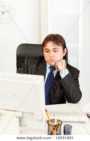 Concentrated modern businessman with head on hand sitting at office desk and looking on monitor