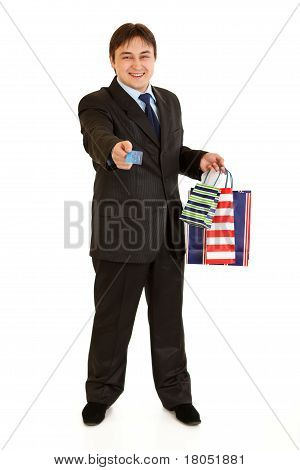 Full length portrait of smiling young businessman with shopping bags giving credit card isolated