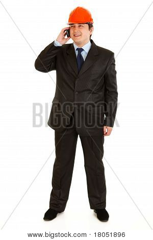 Full length portrait of smiling businessman in helmet on head talking on mobile phone isolated