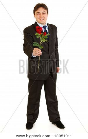 Full length portrait of smiling modern businessman with red rose in hand isolated on white