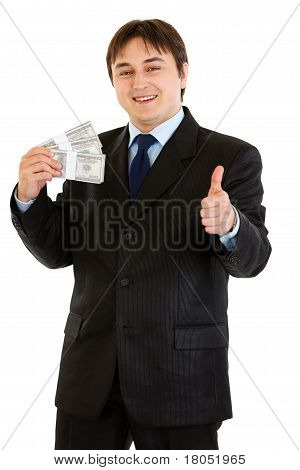 Pleased modern businessman holding stack of dollars and showing thumb up gesture isolated on white