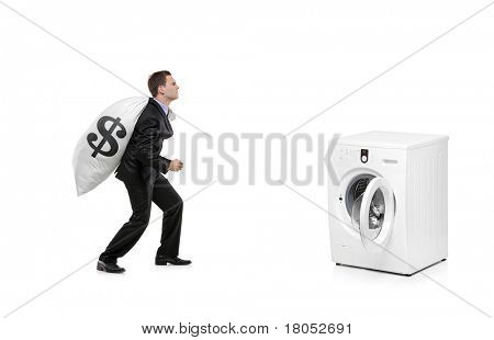 A businessman with money bag on his back going towards a washing machine isolated on white background
