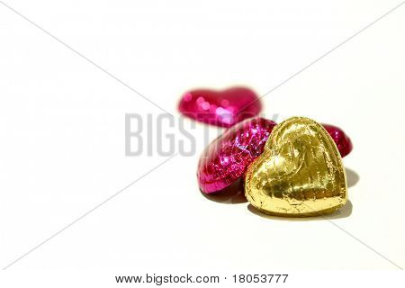 Hearts in a heap : An arrangement of four fuchsia and gold foil covered heartshaped chocolate