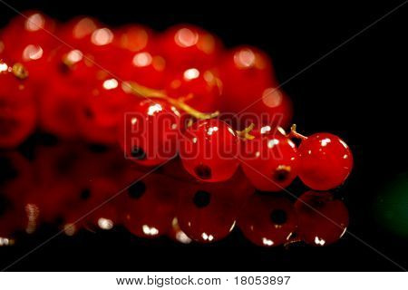Close up of a bunch of redcurrants on black background