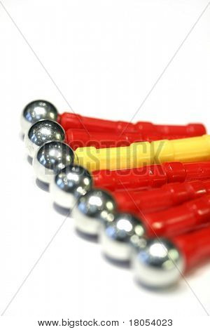 Conceptual image of Unity - Row of red magnets with one single yellow magnet in the middle stuck together unifying strength in numbers and unity in diversity of culture and race