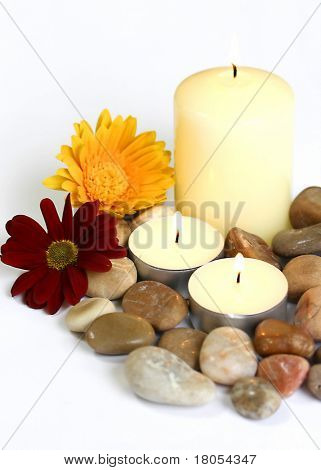 Spiritual and indulgence : Three candles surrounded by shiny pebbles on white plate decorated by a yellow and red flowers, isolated