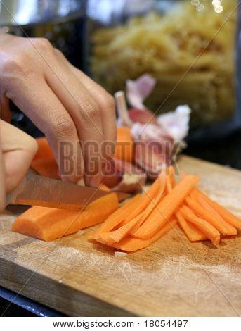 Cerca de un cocinero de cortar las zanahorias en juliana en tablero de madera para picar, profundidad de campo